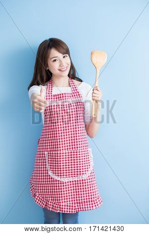 beauty housewife take rice spoon and thumb up isolated on blue background