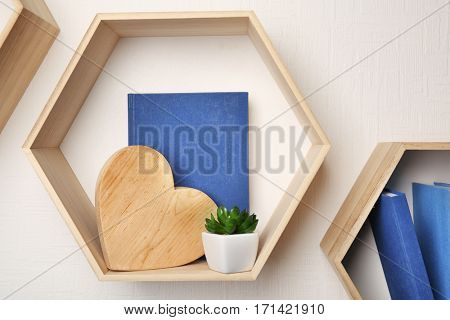 Different books on wooden shelves against light wall