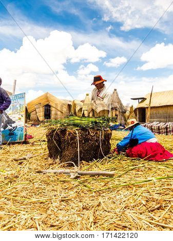 Puno, Peru - December 10, 2011: Two Uros, man and woman, working on Reed miniatures of their huts