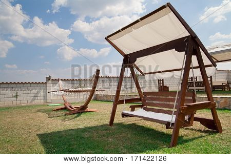 Swinging bench and hammock in the garden. Cloudy sky