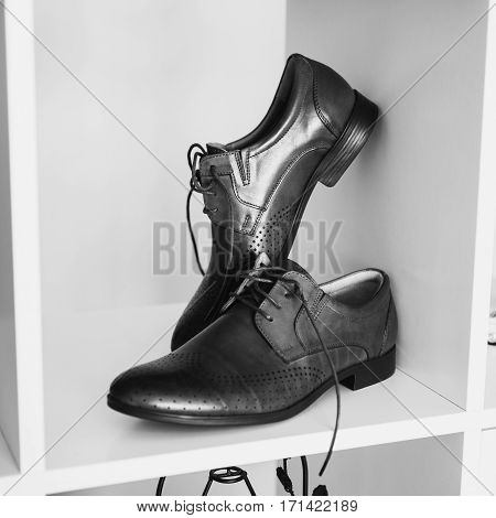 Black and white art photography monochrome man's shoes stand on a shelf. Men's style fashion. Charges groom.