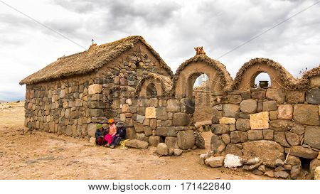 Puno, Peru - December 10, 2011: Three local Children talking in front Small farm near Tombs of Sillustani by Lake Umayo near Puno, Bolivia