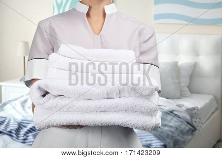 Chambermaid holding clean towels on bedroom background