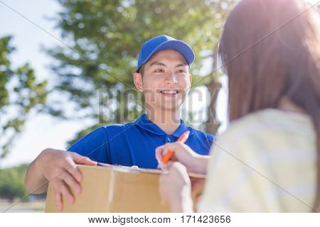 deliveryman stand and smile to customer asian