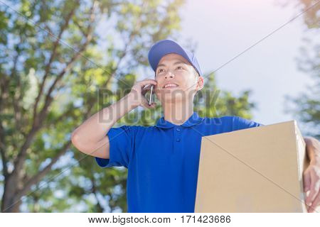 deliveryman hold box and talk on phone asian