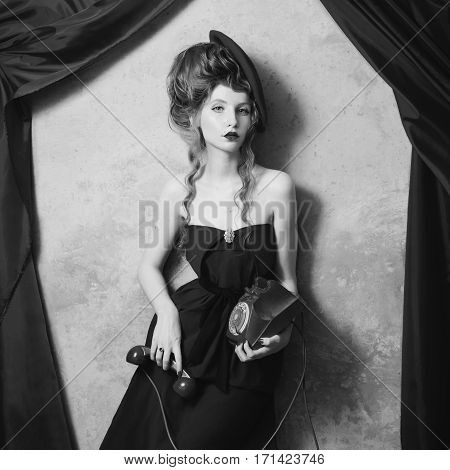 black and white art photography monochrome curly girl in beret her lips smeared lipstick and holding disk telefon. Woman in dress on gray background. Photo in theater actress. Retro film. Art photo