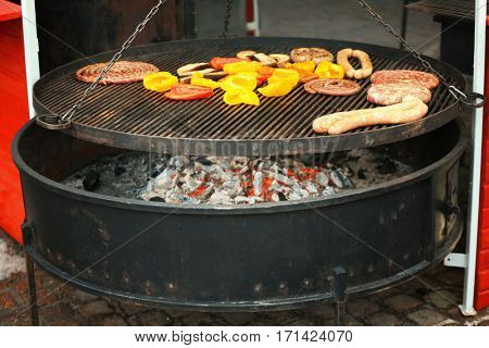 Sweet peppers with sausages on grill grate