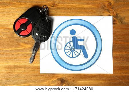 Car key and card with handicap sign on wooden background