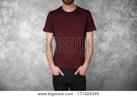 Closeup of man in claret red T-shirt on colour textured wall background