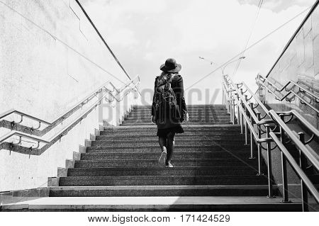 black and white art photography monochrome girl in a hat rises from the underpass. A woman comes out of the subway. Man climbs the stairs.
