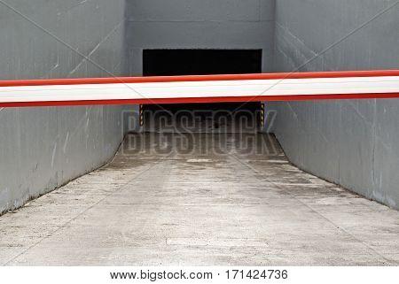 Dark auto garage entrance with rising arm barrier