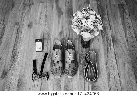 black and white art photography monochrome gray man's shoes on the floor. Men's style fashion. Charges groom. Wedding bouquet of blue and white flowers wedding rings on red box belt and bow tie