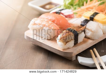 Sushi With Sauce And Wasabi On Old Brown Wood Plate