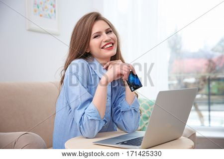 Beautiful young woman doing online shopping at home