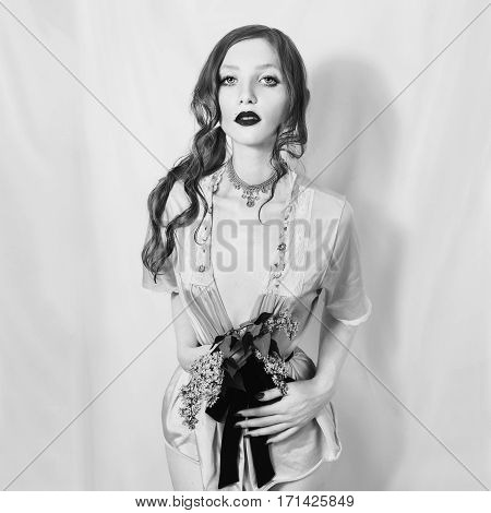 Black and white art photography monochrome sexy girl with the hair gathered in a ponytail holding a lilac flower in the hands. Gothic tattoo model in erotic underwear with a slender waist
