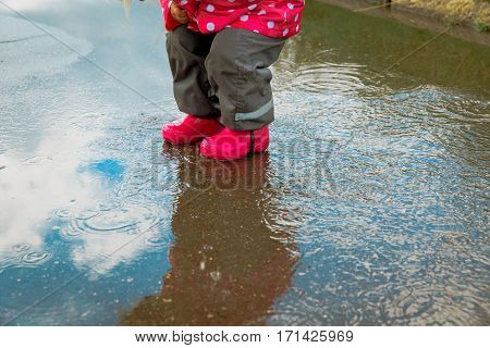 little girl play in water puddle, kids seasonal activities