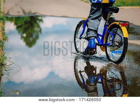 little boy riding bike in water puddle, kids seasonal activities