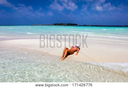 Attractive woman is tanning on a sandbank