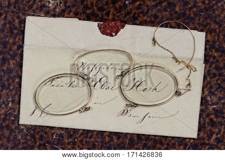 Historic Female Letter Reading Concept: concept of a historic letter reading situation including historic envelope with wax seal, old book cover background and historic female glasses