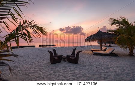 Sunset on a Maldivian beach with rattan chairs and table
