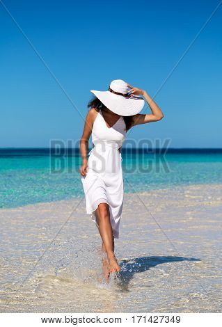 Woman in white walking over a sandbank in the Maldives