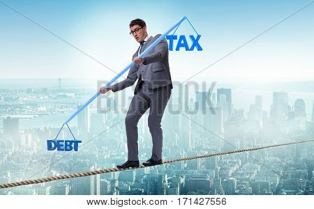 Businessman balancing between debt and tax