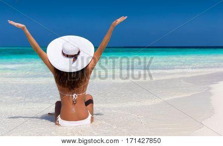 Woman with white hat on a sandbank enjoying the Maldives