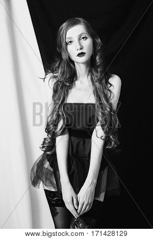 Black and white art photography monochrome girl with long curly hair posing in sexy scarlet lingerie on black and white background. Young woman in stockings garter posing as a model.