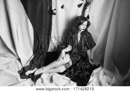 Black and white art photography monochrome girl with blue eyes and pale skin in a coat. Woman with flowers. Curling hair. Gothic style on a white background.