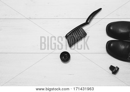 Black and white art photography monochrome black leather boots with shoe maintenance set on a wooden background. Brush for cleaning footwear. Formal business men leather shoes shining