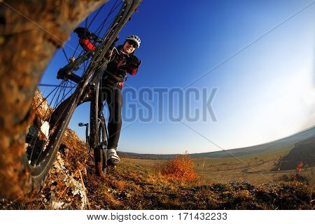 Man on mountain bike on the background of beautiful sunset. Bicycle wheel closeup. Wide angle. Fisheye. Beautiful landscape. Hill, rocks and blue sky. Detail of the bicycle. Wheel. White helmet and black sunglasses.