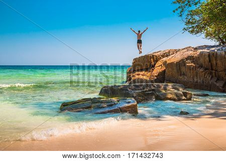 The happy young man jumping off cliff into the ocean. Summer fun lifestyle extreme sport.