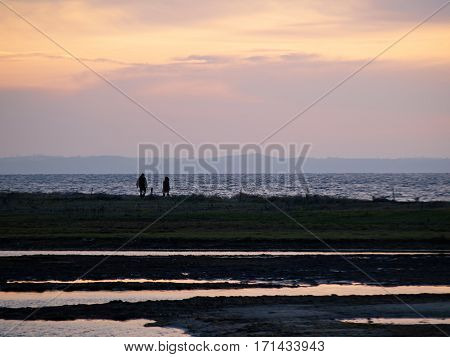Silhouette of a couple walking on the beach at sunset dramatic romantic background image