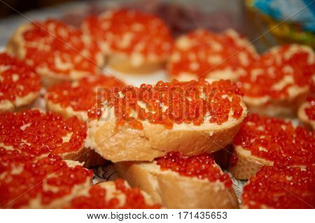 Sandwiches with red caviar on a celebratory table.