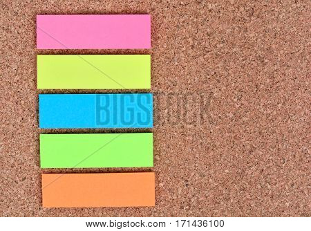Empty five colorful notes on cork background