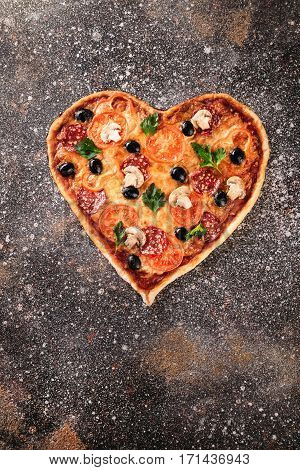 Heart shaped not ready pizza with tomatoes and mozzarella for Valentines Day on vintage concrete background. Food concept of romantic love.