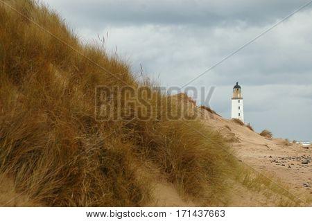 Lighthouse behind sand dunes, taken at Rattray Head, Scotland