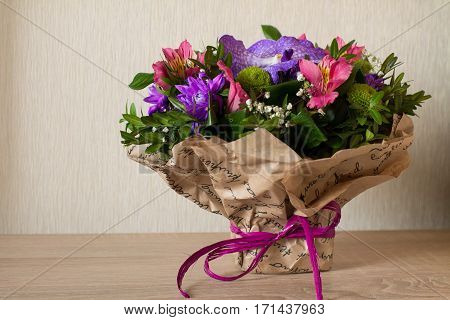 Bouquet of flowers (Purple orchid, alstroemeria, green chrysanthemum, gypsophila and buxus) in paper with bow on wood.