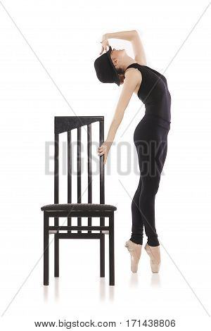 Pretty young ballerina posing with chair on white background