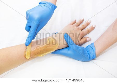 Epilation sugar processes woman passes in a beauty salon