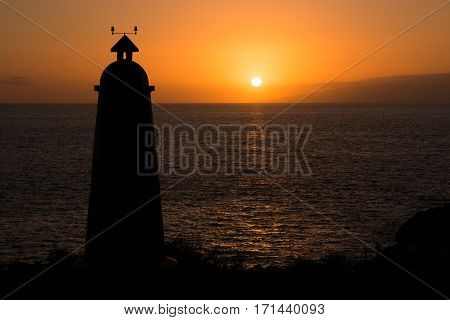 Lighthouse in silhouette at sunset in Tenerife, Spain