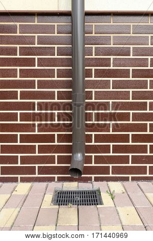 New brown copper drain in a house with brickwork