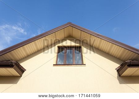 Facade of new house with plastic window and brown rain gutters