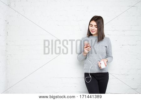 Powerbank In Hands. Woman Playing In Smartphone And Charges Her Phone.