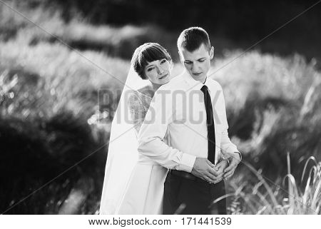 Black and white art photography monochrome wedding couple on nature with sunlight. Love between a man and a woman. Bride in wedding dress. The groom in a suit. Beautiful wedding bouquet