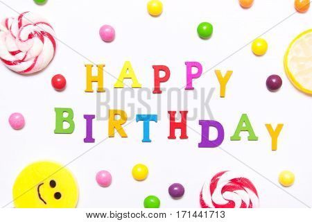 The phrase happy birthday lollipops candy smile on are scattered around the colorful jelly beans on a white background. Top view flat