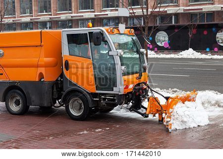 Snow plough cleaning pavements and streets which are covered in snow and mud during heavy snowfall