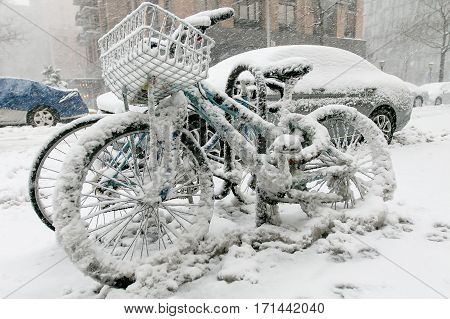 Two bicyles chained to a rack outside are covered in snow during a snowfall in Manhattan.