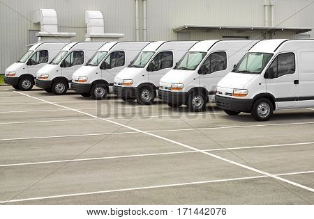 Photograph of white van fleet in the company parking lot