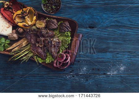 Grilled beef meat with vegetable on a blue wooden background